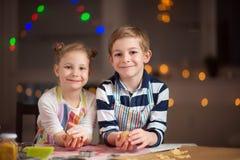 Lyckliga barn som förbereder kakor för jul och nytt år arkivfoton