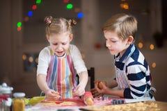 Lyckliga barn som förbereder kakor för jul och nytt år arkivbilder