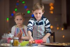 Lyckliga barn som förbereder kakor för jul och nytt år royaltyfria bilder