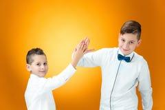 Lyckliga barn som förbi gratulerar, gömma i handflatan med segern Arkivbilder