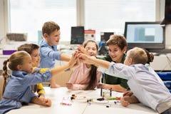 Lyckliga barn som gör höjdpunkt fem på robotteknikskolan arkivfoto
