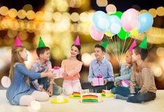 Lyckliga barn som ger gåvor på födelsedagpartiet royaltyfri bild
