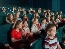 Lyckliga barn som håller ögonen på film på bion fotografering för bildbyråer
