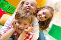 Lyckliga barn som har gyckel hemma Royaltyfria Foton
