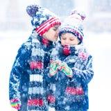 Lyckliga barn som har gyckel med insnöad vinter royaltyfri bild