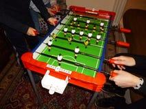 Lyckliga barn som hemma spelar tabellfotboll royaltyfri fotografi