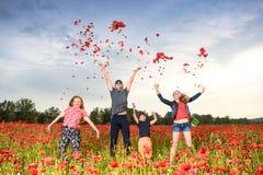 Lyckliga barn som hoppar och kastar kronblad av vallmo royaltyfria bilder