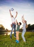 Lyckliga barn som hoppar och spelar med bollen Fotografering för Bildbyråer