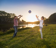 Lyckliga barn som hoppar och spelar med bollen Arkivbild