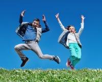 Lyckliga barn som hoppar på äng Fotografering för Bildbyråer