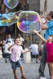 Lyckliga barn som kör in mot en såpbubbla Royaltyfri Bild