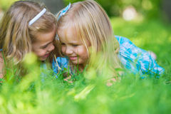Lyckliga barn som kopplar av på grönt gräs i sommar, parkerar arkivbild