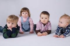 Lyckliga barn som ligger på det vita golvet Arkivfoton