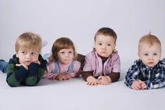 Lyckliga barn som ligger på det vita golvet Royaltyfria Foton