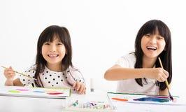 Lyckliga barn som målar i klassrumet Fotografering för Bildbyråer