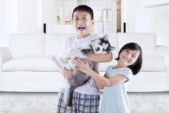 Lyckliga barn som rymmer den skrovliga valpen hemmastadd Arkivfoton