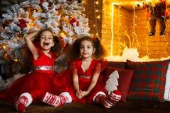 Lyckliga barn som sitter på golvet nära en julgran och en spis Le tvilling- systrar i röd klänning för att krama sig royaltyfri fotografi