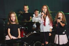 Lyckliga barn som sjunger och spelar musik arkivbild
