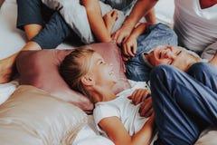 Lyckliga barn som skrattar, medan lägga i säng royaltyfri fotografi