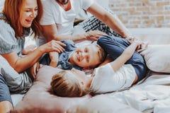 Lyckliga barn som skrattar, medan spela med föräldrar arkivfoto