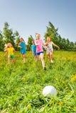 Lyckliga barn som spelar fotboll i grönt fält royaltyfri bild