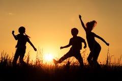 Lyckliga barn som spelar i parkera Arkivbilder