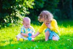 Lyckliga barn som spelar i trädgården med leksaken, klumpa ihop sig Royaltyfria Bilder