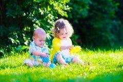 Lyckliga barn som spelar i trädgården med leksaken, klumpa ihop sig Fotografering för Bildbyråer