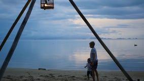 Lyckliga barn som spelar på kusten arkivfilmer