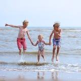 Lyckliga barn som spelar på stranden royaltyfri fotografi