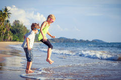 Lyckliga barn som spelar på stranden på dagtiden Arkivbilder