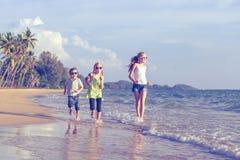 Lyckliga barn som spelar på stranden på dagtiden Arkivfoto
