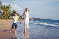 Lyckliga barn som spelar på stranden på dagtiden Royaltyfri Bild