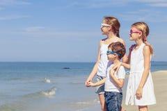 Lyckliga barn som spelar på stranden på dagtiden Arkivfoton