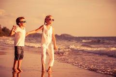 Lyckliga barn som spelar på stranden på dagtiden Royaltyfri Foto