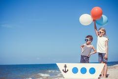 Lyckliga barn som spelar på stranden på dagtiden Royaltyfria Bilder