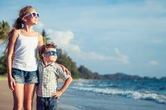 Lyckliga barn som spelar på stranden på dagtiden Fotografering för Bildbyråer