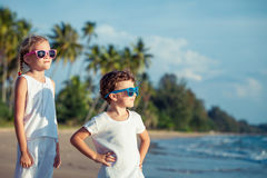 Lyckliga barn som spelar på stranden på dagtiden Arkivbild