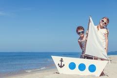 Lyckliga barn som spelar på stranden på dagtiden Royaltyfria Foton