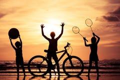 Lyckliga barn som spelar på stranden på solnedgångtiden Arkivbilder