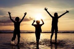 Lyckliga barn som spelar på stranden på solnedgångtiden Royaltyfria Bilder
