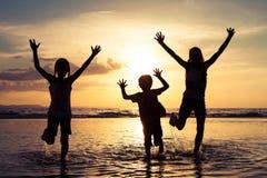 Lyckliga barn som spelar på stranden på solnedgångtiden Arkivbild