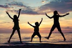 Lyckliga barn som spelar på stranden på solnedgångtiden Royaltyfri Foto