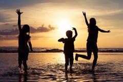 Lyckliga barn som spelar på stranden på solnedgångtiden Arkivfoto