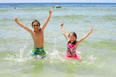 Lyckliga barn som står i vatten med lyftta armar Arkivfoto