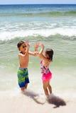 Lyckliga barn som står, i vatten och att spela Arkivbilder