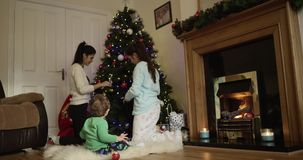 Lyckliga barn som tillsammans dekorerar trädet för jul och för nytt år Förtjusande son som ser hans moder och äter äpplet lager videofilmer