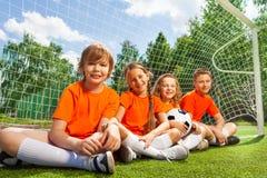 Lyckliga barn som tillsammans sitter på fältgräs royaltyfria bilder