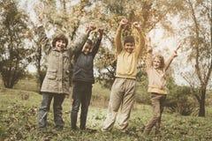 Lyckliga barn som tycker om i parkera Lyftt ställning för barn händer Royaltyfria Foton