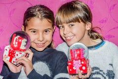 Lyckliga barnflickor i gåva för jordklot för julhatt en hållande glass av Arkivbilder